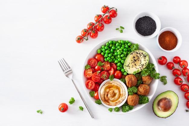 Zdrowa wegańska miska na lunch z falafelowym hummusem pomidorowym z groszkiem awokado