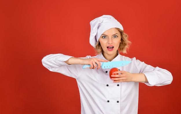 Zdrowa, wegetariańska, dieta warzywna, dieta, odżywianie, poprawna koncepcja żywności - profesjonalny kucharz trzyma w dłoniach pomidor i nóż. szef kuchni w białym mundurze kroi pomidora. skopiuj miejsce.