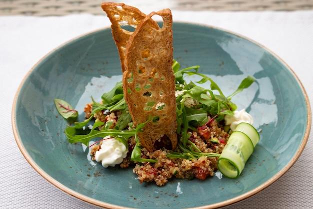 Zdrowa włoska sałatka z pestek komosy ryżowej, pomidorów i rukoli z serkiem śmietankowym i grzanką. haute cuisine w restauracji na ulicznym tarasie street