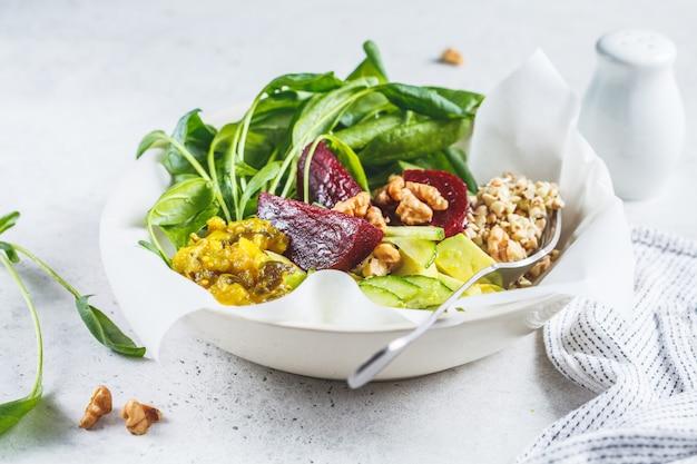Zdrowa zielona sałatka z buraczkami, smakiem i kiełkami zielonej gryki. koncepcja zdrowego wegańskiego jedzenia.