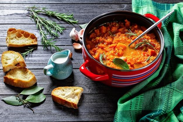 Zdrowa zupa dyniowa z dietą ketonową w czerwonym rondlu z łyżką do nalewania na drewnianej powierzchni z tostowym chlebem, śmietaną, czosnkiem, liściem laurowym, rozmarynem, widok z góry, zbliżenie