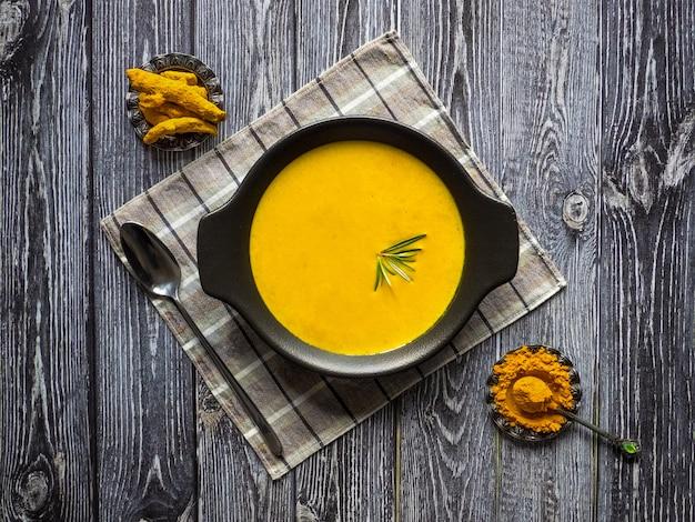 Zdrowa zupa krem kurkuma na czarny drewniany