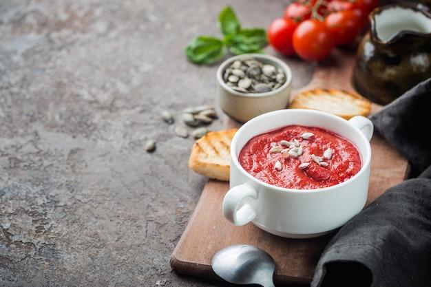 Zdrowa zupa pomidorowa w białej misce ze śmietaną i pestkami słonecznika