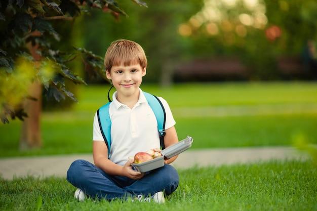 Zdrowa żywność dla ucznia. ładny chłopiec jedzenie owoców na świeżym powietrzu w pobliżu szkoły.