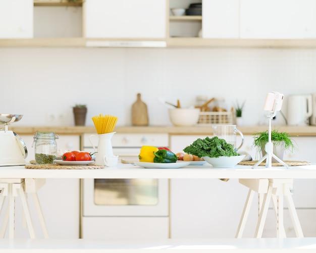 Zdrowa żywność do gotowania włoskiego makaronu i warzyw na stole kuchennym w nowoczesnym, jasnym mieszkaniu