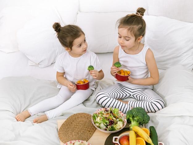 Zdrowa żywność, dzieci jedzą owoce i warzywa.