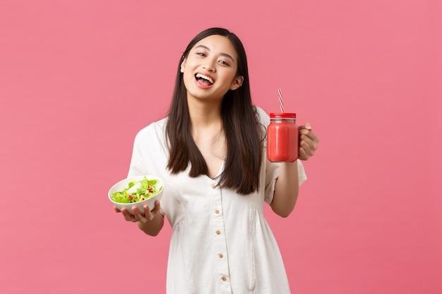 Zdrowa żywność, emocje i koncepcja letniego stylu życia. entuzjastyczna i optymistyczna śliczna azjatka pełna energii, jedząca smaczną świeżą sałatkę i pijąca koktajl, uśmiechając się do kamery szczęśliwe, różowe tło.