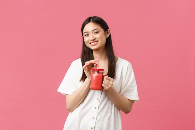 Zdrowa żywność, emocje i koncepcja letniego stylu życia. uśmiechnięta ładna wysportowana azjatka dbająca o ciało, pijąca świeży koktajl ze szkła i wpatrująca się w zadowoloną kamerę, różowe tło.