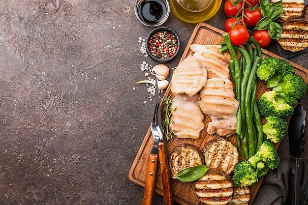 Zdrowa żywność grillowany kurczak z warzywami na desce do krojenia na ciemnej powierzchni, widok z góry