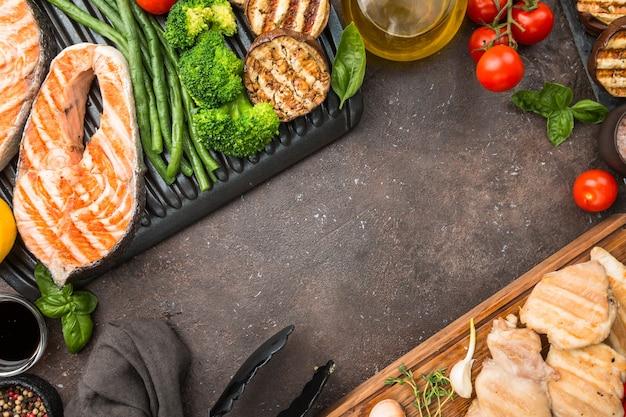 Zdrowa żywność grillowany stek z łososia, kurczak i warzywa na ciemnej powierzchni, widok z góry