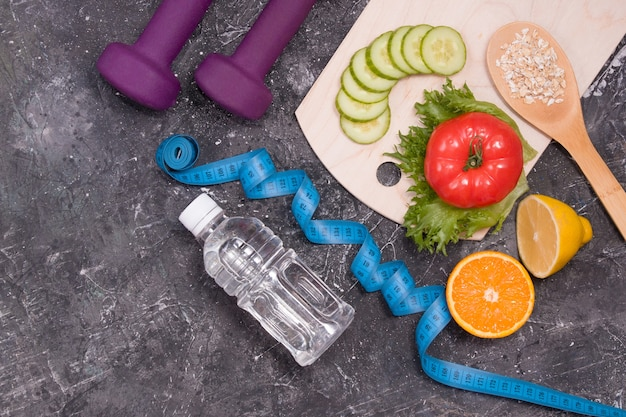 Zdrowa żywność hantle butelka wody i taśma miernicza na ciemnym tle koncepcja odchudzania