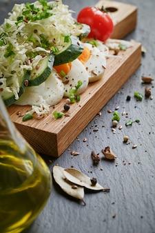Zdrowa żywność i składniki z pomidorem, ogórkiem, kapustą, zieloną cebulą, jajkiem i przyprawami na ciemno