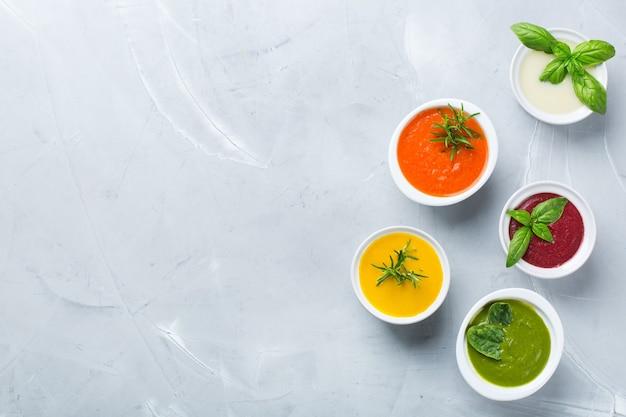 Zdrowa żywność, koncepcja czystego jedzenia. różnorodność kolorowych sezonowych jesiennych warzyw kremowych zup ze składnikami. dynia, brokuły, marchew, burak, ziemniak, szpinak pomidorowy. płaski układanie, kopiowanie przestrzeni