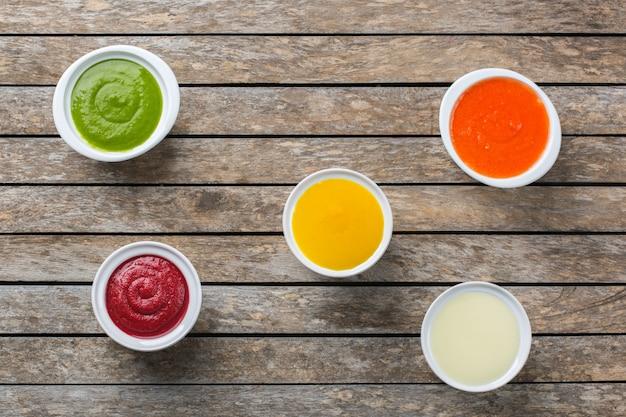 Zdrowa żywność, koncepcja czystego jedzenia. różnorodność kolorowych sezonowych jesiennych warzyw kremowych zup ze składnikami. dynia, brokuły, marchewka, burak, ziemniak, szpinak pomidorowy. płaskie ułożenie