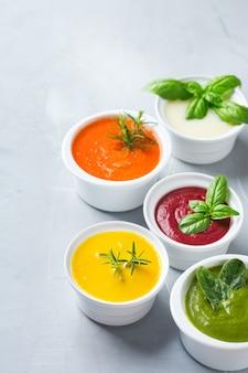 Zdrowa żywność, koncepcja czystego jedzenia. różnorodność kolorowych sezonowych jesiennych warzyw kremowych zup ze składnikami. dynia, brokuły, marchewka, burak, ziemniak, szpinak pomidorowy