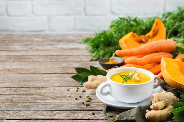 Zdrowa żywność, koncepcja czystego jedzenia. sezonowe pikantne jesienne warzywa kremowa zupa z dyni i marchwi ze składnikami na rustykalnym drewnianym stole. skopiuj tło przestrzeni