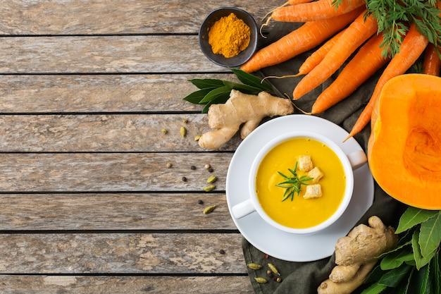 Zdrowa żywność, koncepcja czystego jedzenia. sezonowe pikantne jesienne warzywa kremowa zupa z dyni i marchwi ze składnikami na rustykalnym drewnianym stole. widok z góry na płaskie tło kopii zapasowej