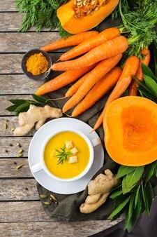Zdrowa żywność, koncepcja czystego jedzenia. sezonowe pikantne jesienne warzywa kremowa zupa z dyni i marchwi ze składnikami na rustykalnym drewnianym stole. widok z góry na płaskie tło