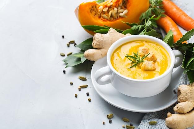 Zdrowa żywność, koncepcja czystego jedzenia. sezonowe pikantne jesienne warzywa kremowa zupa z dyni i marchwi ze składnikami na stole. skopiuj tło przestrzeni