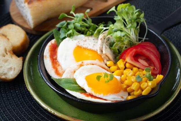 Zdrowa żywność koncepcja super breakfast jajka sadzone i sałata mikro-zielona z kukurydzą i pomidorami na patelni żelaznej skillet z miejscem na kopię