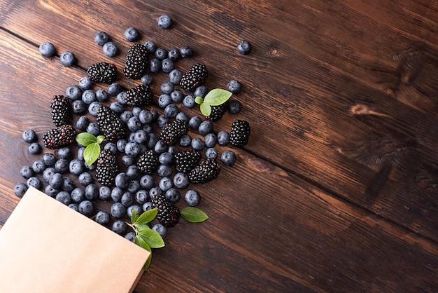 Zdrowa żywność, papierowa torba na zakupy z rozlewającymi się jagodami i jeżynami na ciemnym tle drewnianych, letnie jagody.