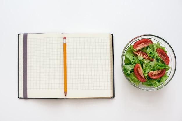 Zdrowa żywność przygotowująca widok z góry książki kucharskiej na przepis w pobliżu sałatki