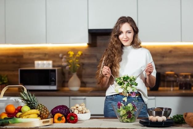 Zdrowa żywność - sałatka jarzynowa. dieta. pojęcie diety. młoda kędzierzawa kobieta przygotowywa jarzynowej sałatki w jej kuchni. pojęcie zdrowego stylu życia, piękna uśmiechnięta kobieta mieszał warzywa.