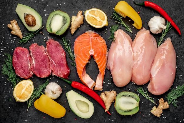 Zdrowa żywność - surowa wołowina, łosoś, filet z kurczaka, owoce i warzywa.