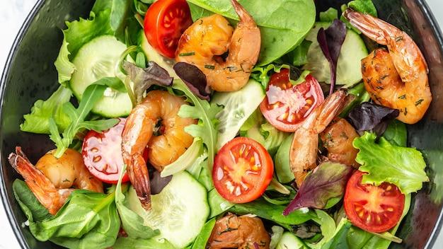 Zdrowa żywność świeże sałatka z owoców morza z wędzonych krewetek, pomidorów koktajlowych, ogórka i mieszanych liści. koncepcja zdrowego odżywiania. dieta detoksykująca. tło przepis żywności. ścieśniać.