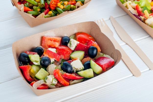 Zdrowa żywność w jednorazowych ekologicznych opakowaniach do żywności. sałatka jarzynowa w pojemniku na żywność z brązowego papieru pakowego na drewnianej powierzchni.