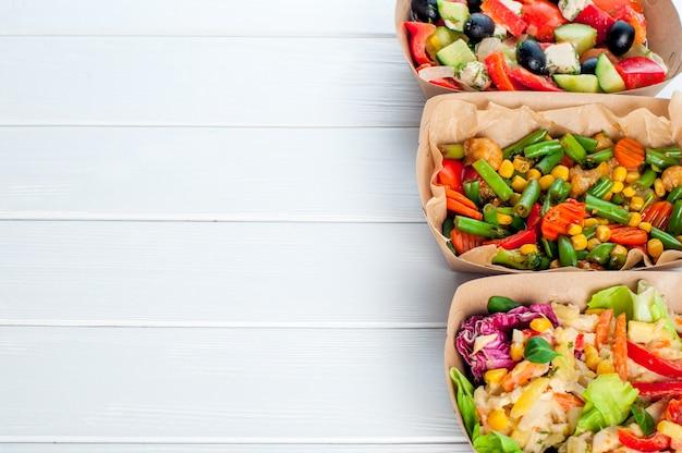 Zdrowa żywność w jednorazowych ekologicznych opakowaniach do żywności. sałatki warzywne w pojemnikach na żywność z brązowego papieru pakowego na białym tle drewnianych z miejsca na kopię.