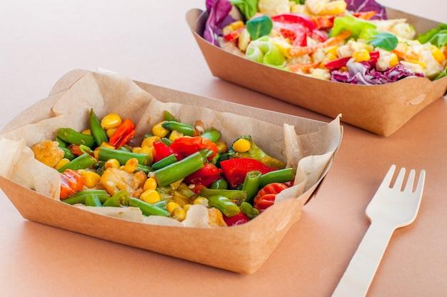 Zdrowa żywność w jednorazowych ekologicznych opakowaniach do żywności. warzywa gotowane na parze w pojemniku na żywność z brązowego papieru pakowego na drewnianej powierzchni.