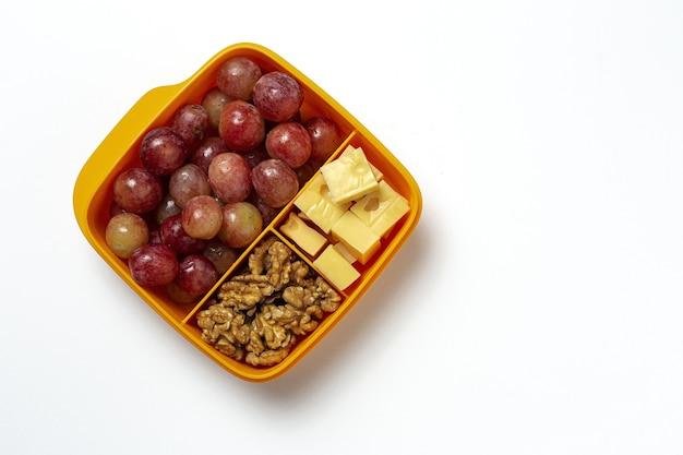 Zdrowa żywność w plastikowych pojemnikach gotowych do spożycia z serem, winogronami i orzechami włoskimi na stole roboczym