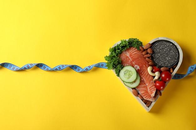 Zdrowa żywność w sercu i miarkę na żółtym tle