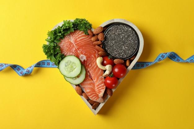 Zdrowa żywność w sercu i taśma miernicza na żółtym tle
