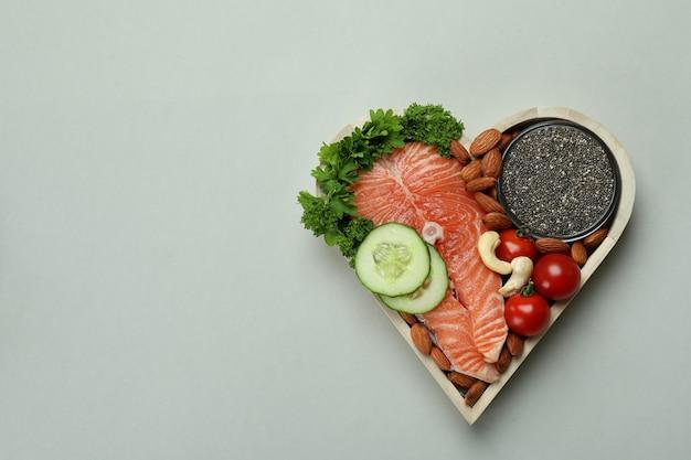 Zdrowa żywność w sercu na jasnoszarym tle