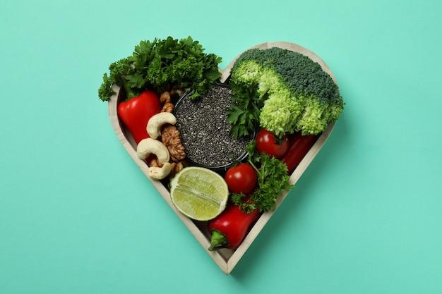 Zdrowa żywność w sercu na miętowym tle, widok z góry