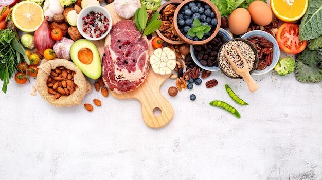 Zdrowa żywność z drewnianą deską do krojenia na białym marmurowym tle