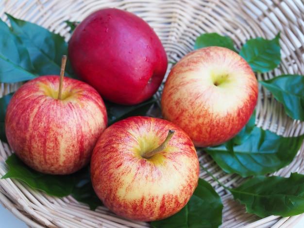 Zdrowa żywność z jabłkami, czerwonymi owocami w bambusowych koszach i zielonych liściach