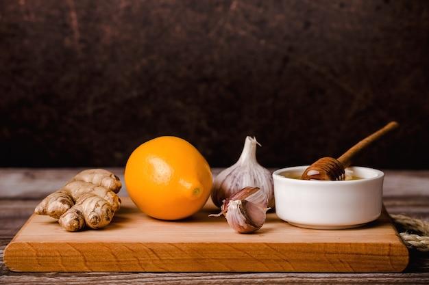 Zdrowa żywność, zestaw odpornościowy, witamina c-miód, korzeń imbiru, cytryna, czosnek, na desce, brązowe tło