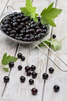 Zdrowa żywnośćagriculturezbiór i koncepcja owoców świeże dojrzałe czarne porzeczki na starym drewnianym tle