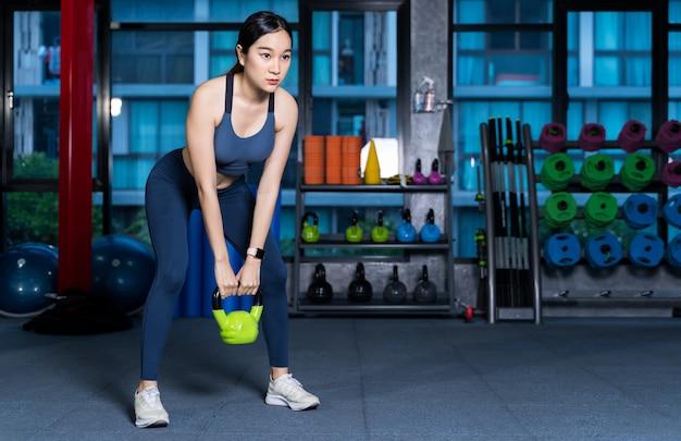 Zdrowe azjatyckie kobiety robią sprzęt do podnoszenia,