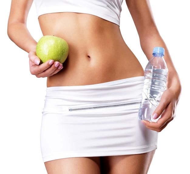 Zdrowe ciało kobiety z jabłkiem i butelką wody. zdrowe fitness i koncepcja stylu życia odżywiania.