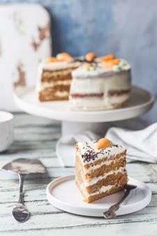 Zdrowe domowe ciasto marchewkowe z kremem serowym na białym drewnianym stole