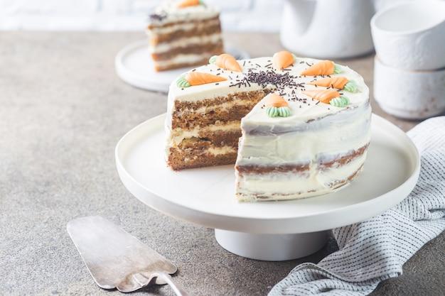 Zdrowe domowe ciasto marchewkowe z kremem serowym na jasnym kamieniu