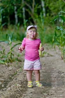 Zdrowe dzieciństwo w harmonii z naturą - szczęśliwa dziewczyna pokazuje język w polu kukurydzy