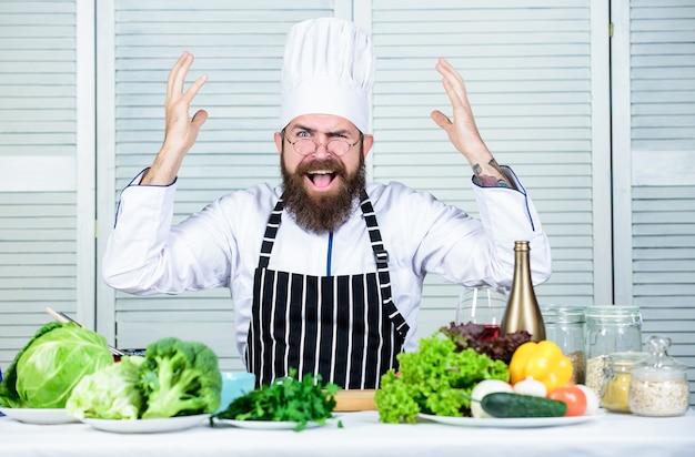 Zdrowe gotowanie żywności. dojrzały hipster z brodą. sałatka wegetariańska ze świeżymi warzywami. dieta żywności ekologicznej. kuchnia kulinarna. witamina. zły brodaty mężczyzna. przepis szefa kuchni. pod kontrolą.
