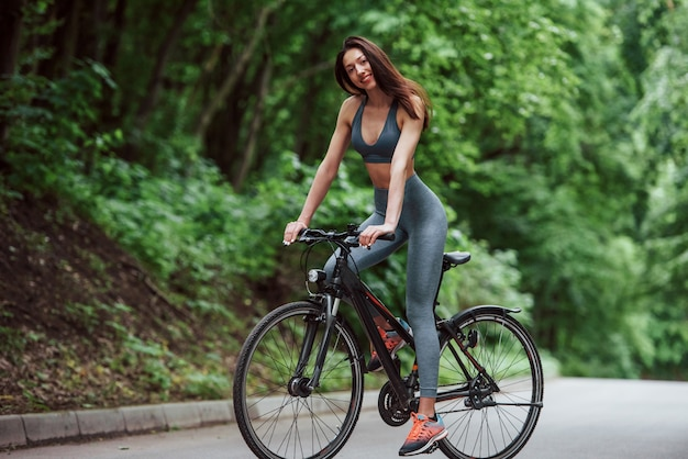 Zdrowe i przyjemne spędzanie czasu. kobieta rowerzysta na rowerze na drodze asfaltowej w lesie w ciągu dnia