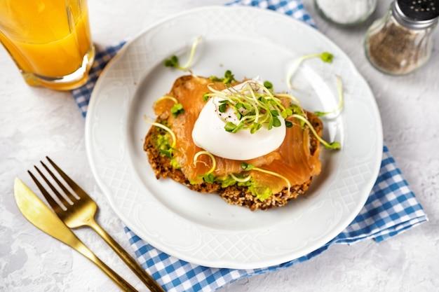 Zdrowe i pyszne tosty z awokado, solonym łososiem, jajkiem w koszulce