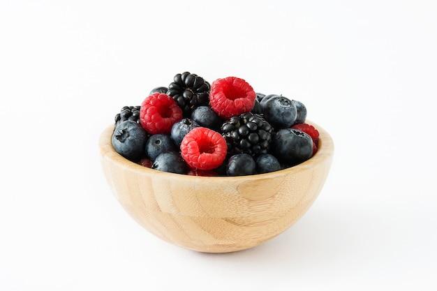 Zdrowe jagody na drewnianym pucharze odizolowywającym